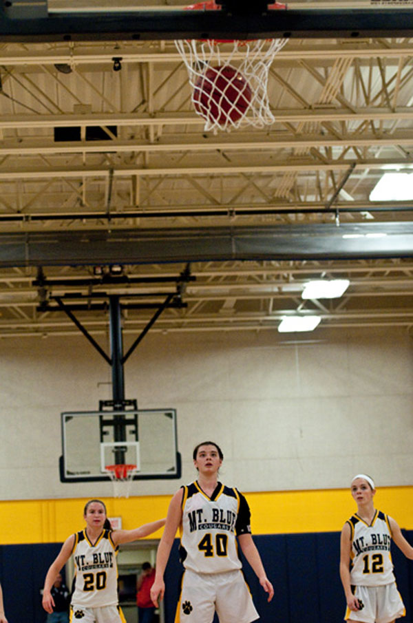 Mt. Blue's Addie Brinkman (40) watches her free throw fall throw the net while teammates Mackenzie Conlogue (20) and Caitlin Kane (12) look on.