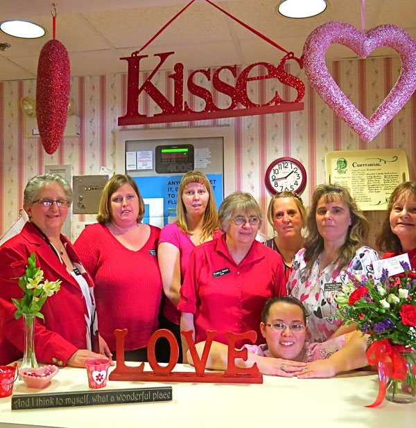 The Pierce House staff with today's festive traditional pink and red Valentine decorations. From left to right Darlene Mooar, Administrator; Carmen Burke, Residential Care Coordinator; Heather Remick, Activity Director; Pammie Smilies, Head Cook; Tracey Pease, Residential Care Specialist; Julie Gilbert, Residential Care Specialist; Pam Hodge, Assistant Administrator. In front Kaylie Lovejoy, Residential Care Specialist.