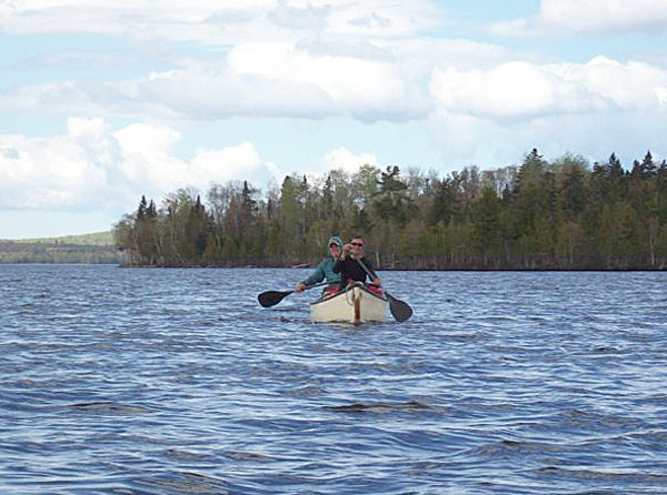 Emma Carlson and Emily Rooney paddle across Rangeley Lake on Saturday.