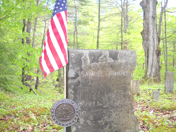 A flag flies from the grave of a Revolutionary War veteran.  [Description of event by Ray Hamilton] On May 17, the Ancient Ones Of Maine had a ceremony and placed a proper Revolutionary War flag holder on a grave in Canton, Maine. The grave belongs to Samuel Simmons. He is buried in his family cemetery beside Meadowview Road. As I placed the new marker I thanked Samuel for his service and then fifteen or so A/O members fired a volley from muskets and rifles. The barrage would have reminded Samuel of some of the battles he had fought in. Every flintlock went off together and the huge gray cloud hung over the cemetery momentarily and then a gust of wind moved the cloud off into the distance. As I stood in reverence I couldn't help but think how that cloud is a lot like our time here on earth.   The Ancient Ones of Maine are a pre-1840 living history group who formed in the early 1980's. They meet in Canton at least twice a year to live the history. Ray Hamilton is a member and writes a monthly blackpowder/hunting column for the Northwood's Sporting Journal. He can be found in Livermore.