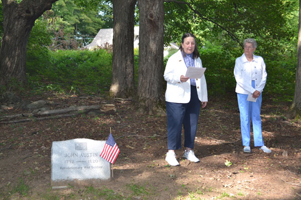 Julia Nouvertne, regent of the Colonial Daugters Chapter, DAR, speaks to a small assembly at the grave marker indicating the location of the 'Old Burying Ground.' Beside her is Nancy Flick, the chapter's chaplain.