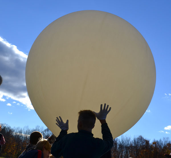 Mt. Blue Campus biology student Thomas Wing, holds the balloon as its inflated for launch on Thursday morning.