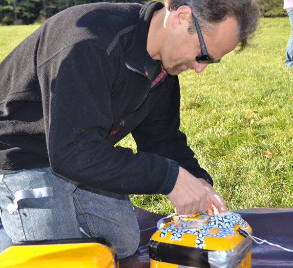 Teacher Doug Hodum attaches seeds to the balloon's payload. Students are teating effects of high altitude, extreme temperatures and ultra violet light on a variety of items .