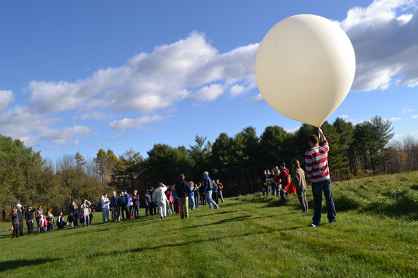 Alex Gilbert holds the balloon as students countdown towards launch.