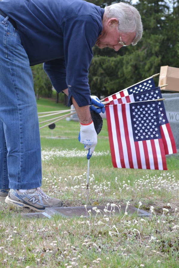 American Legion Post 28 Commander David Targett place a flag at the grave of a veteran at Fairview Cemetery in Farmington on Sunday.