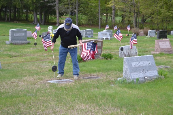 Veteran Ron Smith of  Temple, places a flag at a veteran's grave in Fairview Cemetery in Farmington on Sunday.