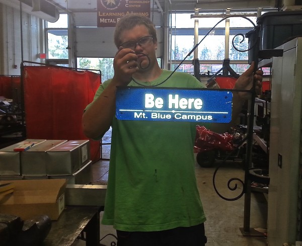 Mt. Blue High School senior Ben Emery  shows the other side of the sign which read Be Here, part of the Campus Code.