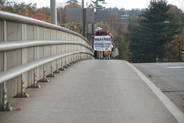 Carrying the Walk 4 Peace sign, Peter Cook of Starks carries the Walk for Peace sign followed by more than a dozen as they cross Center Bridge in Farmington on their way to South Berwick.