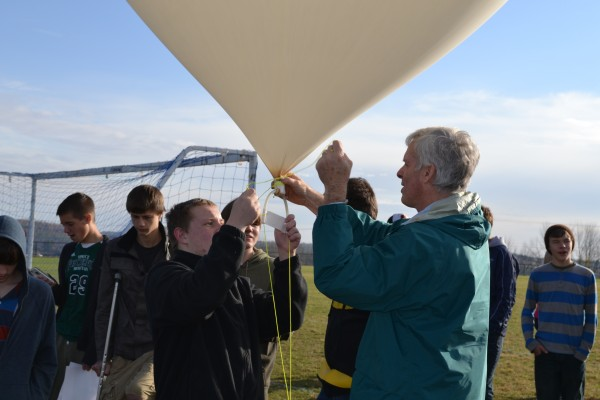 Mt. Blue High School student Austin Seeley helps University of Maine professor Rick Eason tie off the weather balloon and attach its payload before launch on Tuesday.