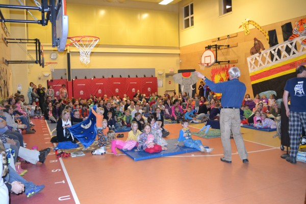 Author/Illustrator Chris Van Dusen reads an audience of students and their parents.