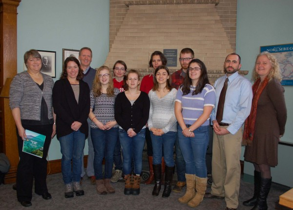 UMF students and faculty present tokens of friendship from Lac-Megantic Public Library to Maurie Stockford, director of Farmington Public Library (far left.)  Left to right (back row) Brad Dearden, associate professor of geography; Rachel Mas, language assistant; Zhanna Ivanova and Tobias Logan. (Front row) Maurie Stockford, director of Farmington Public Library; Nicole Kellett, assistant professor of anthropology; Emmaline Waldron; Pauline Lefeuvre, exchange student from France; Sarah Gould; Celeste Carpenter; Clint Bruce, assistant professor of French and Linda Beck, professor of political science and director of UMF International and Global Studies Program.