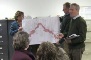 Darryl Sterling addresses residents at Tuesday's public hearing as Town Manager Rhonda Irish and Selectboard Chair D. Scott Taylor hold a map showing the district that will benefit from Community Development Block Grant funding. (Photo by Mt. Blue TV)