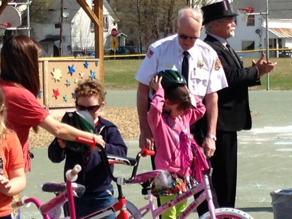 Students try on their new bike helmets while Gerry Gilman addresses the assembly.