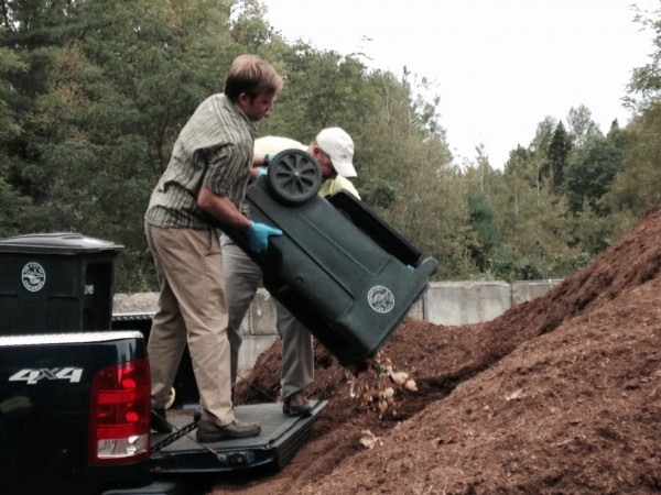 Associate Professor Luke Kellett, UMF sustainability coordinator and Professor Tom Eastler pour food scraps into the Farmington Compost Cooperative's pile at the transfer station.