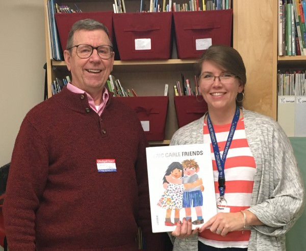 Dennis O'Neil from the Farmington Rotary Club poses with Mallett Pre-K teacher, Erika Neal, who holds the first book provided in October to the 64 children enrolled at Mallett Pre-K.