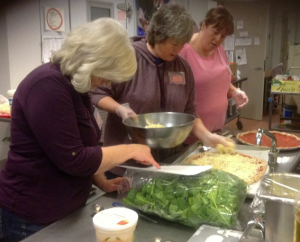 Staff preparing a fresh spinach and caramelized onion pizza.