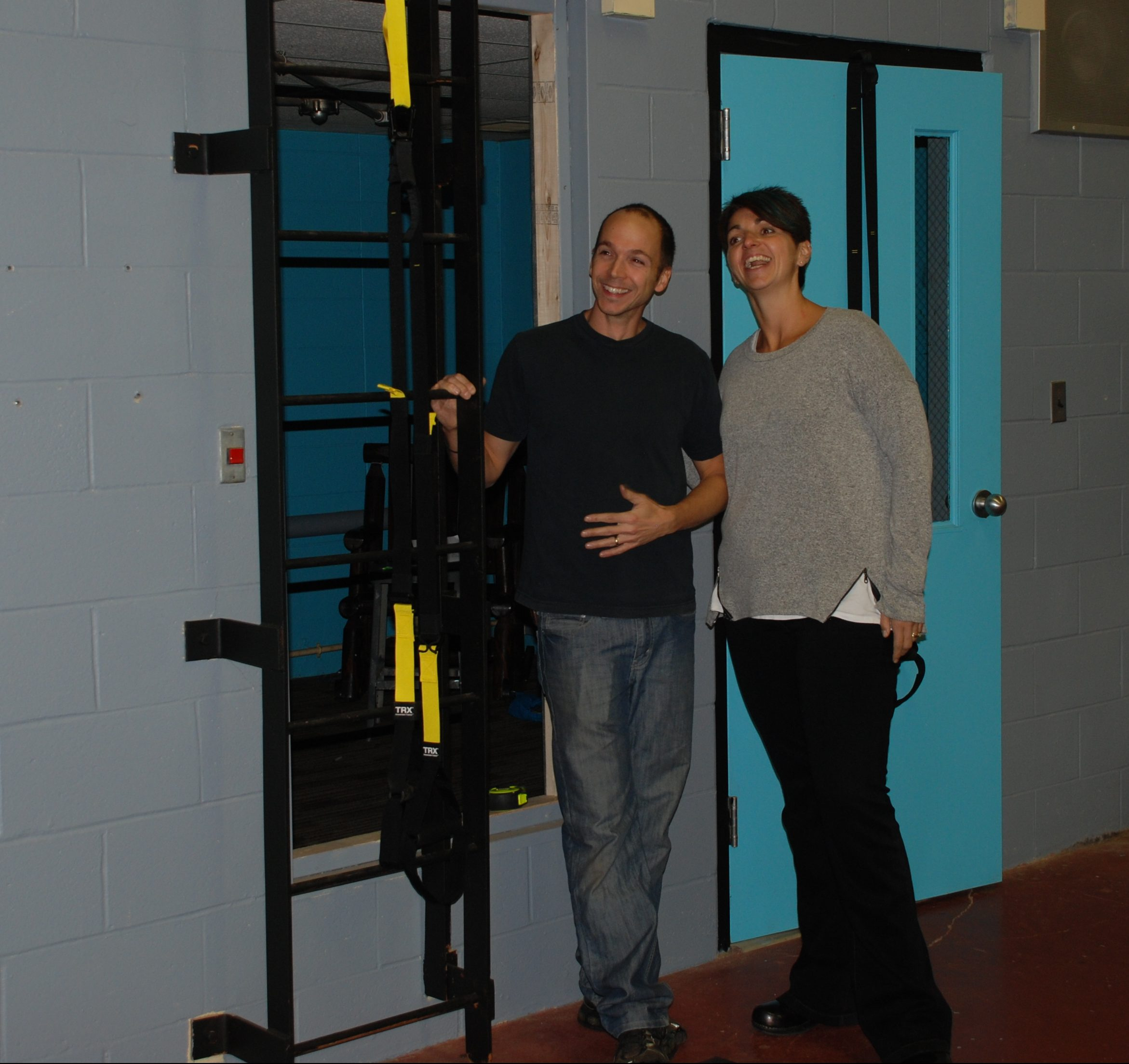 Dominic and Betsy Mancine beside a TRX suspension training rig.