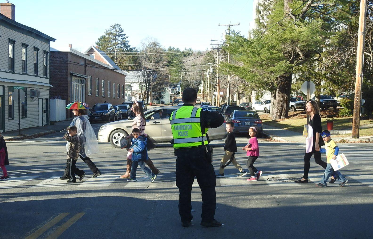 Farmington Police Officer Justin Blais waves as students walk across High Street.