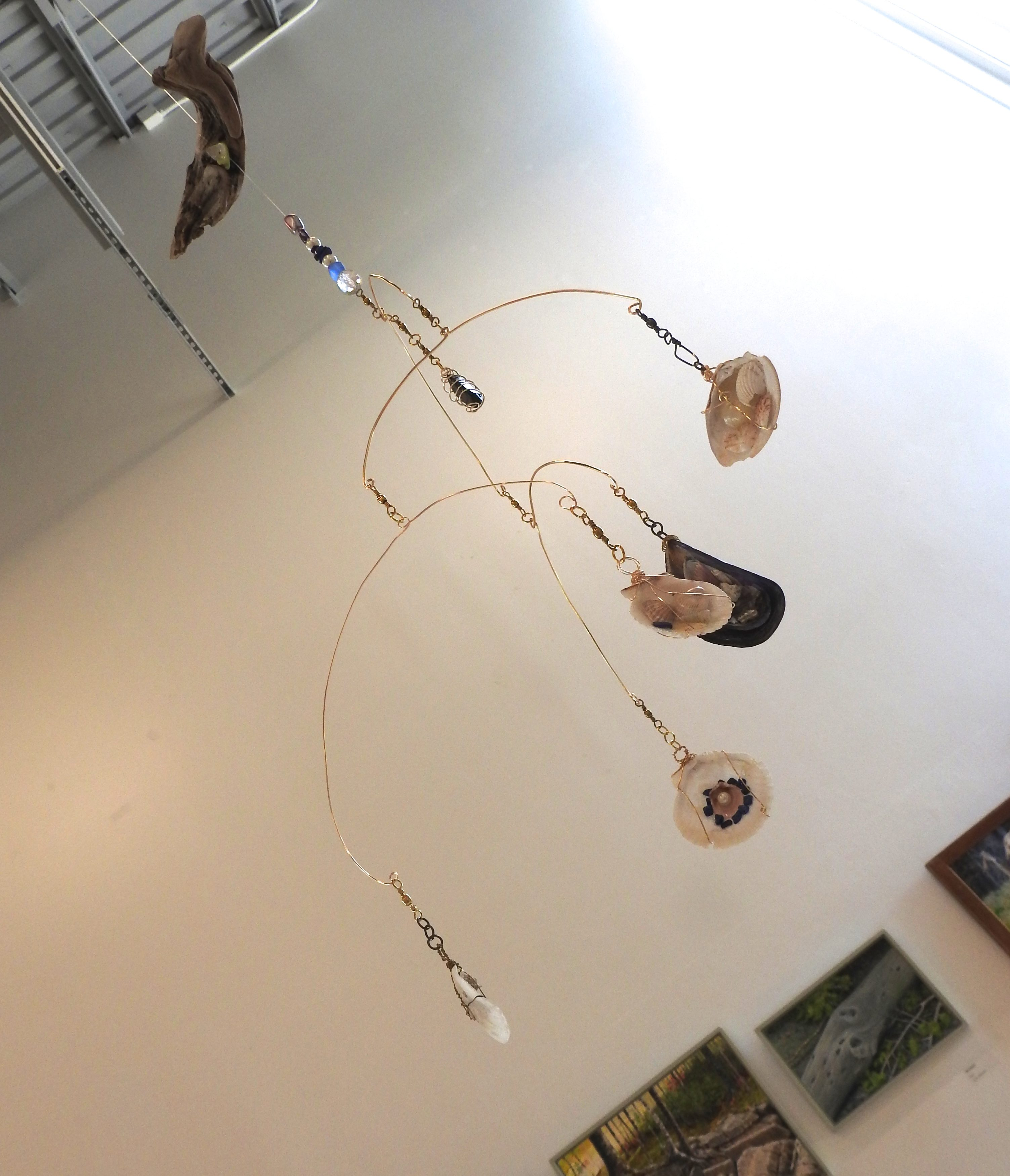 A Wire Mobile Of Driftwood, Shells And Beads